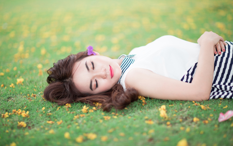 Relaxed woman laying in spring grass with flowers in her hair