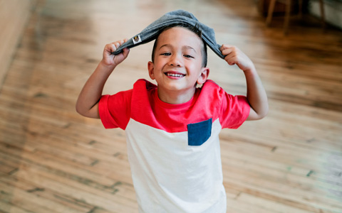 Happy kid in kitchen, smiling and holding dish towel