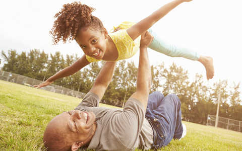 father lifting his daughter over his head, happy and playing in the park