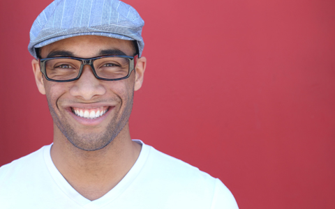 man with newsboy cap, trendy black glasses, and white v neck shirt smiling at the camera