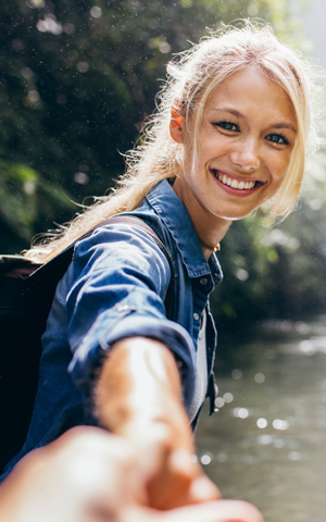 young blonde woman extending her hand and reaching for someone to go on an adventure with her outside