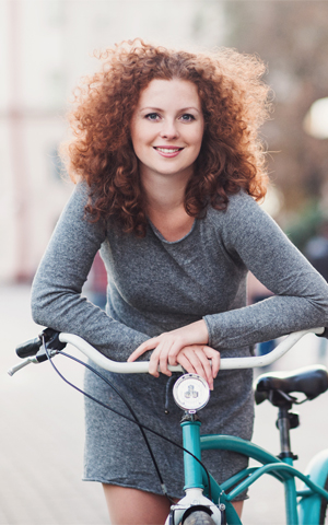 curly, red haired woman riding her bike and smiling
