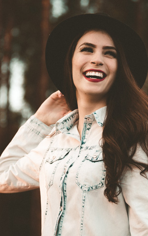 Woman in denim shirt and black hat, smiliting outdoors
