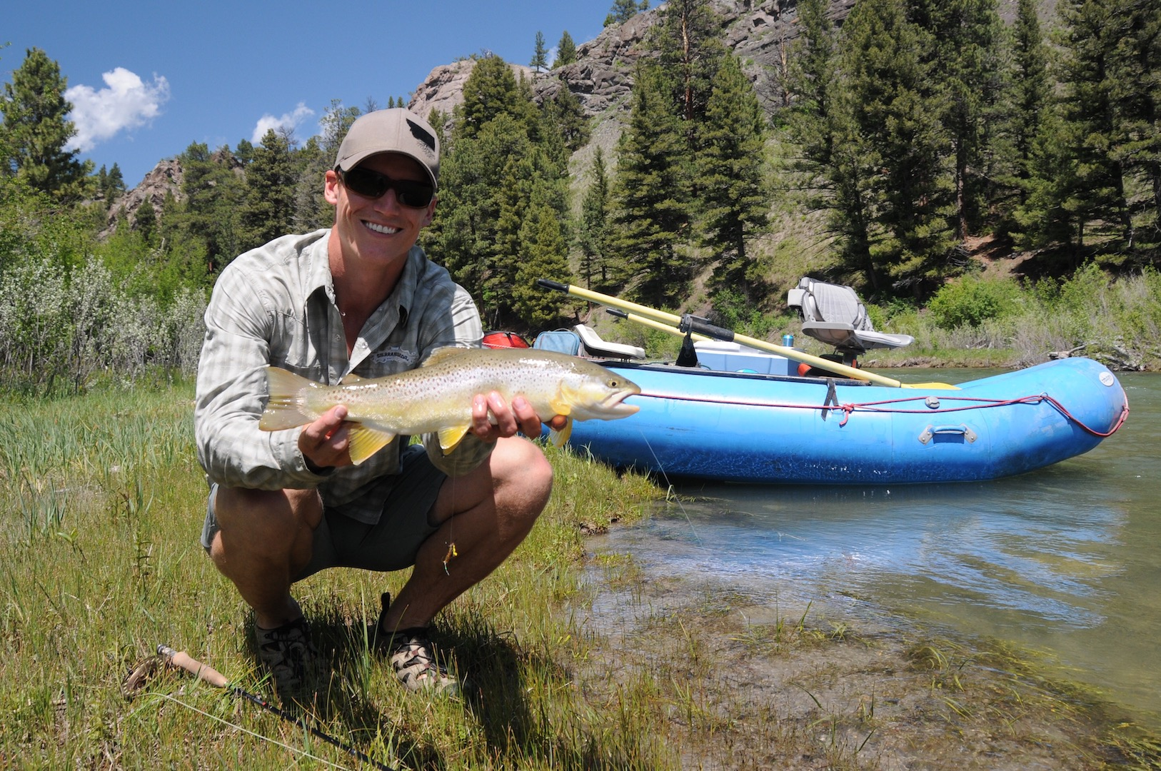 Dan McFarland, DDS with a fish in his hands and mountains in the background